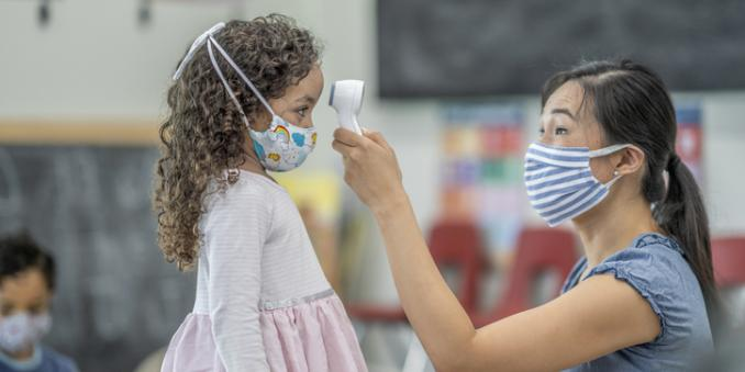 Woman taking girl's temperature