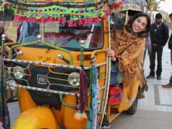 Image of woman in sari driving a yellow 3 wheel auto with very colorful scarves and decorations on it, down a street with a woman setting and two men standing with two trees in an open area