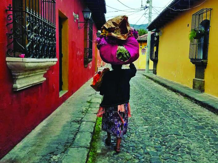 Image of woman in walking down an on old, but colorful, street in Guatemala, carrying bags in left arm and many bags on top of head