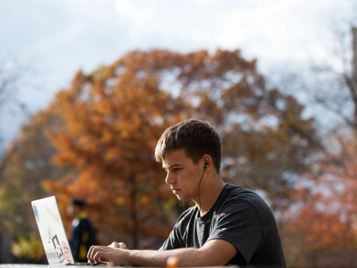 Student sitting outside on computer