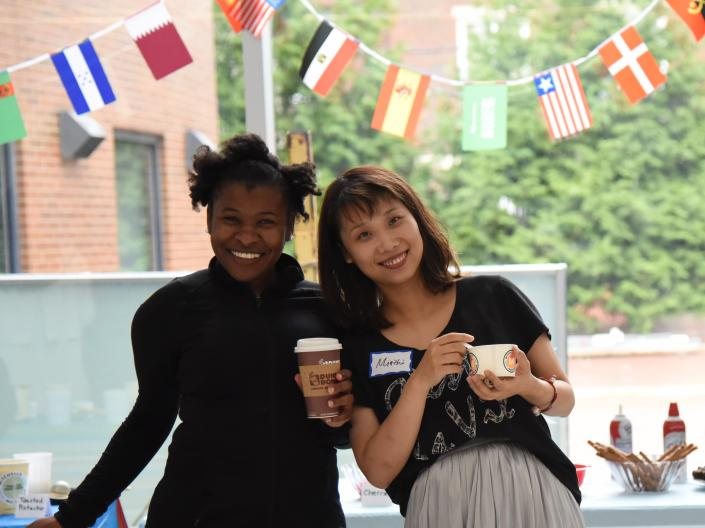 Two social work students pose in front of various country flags