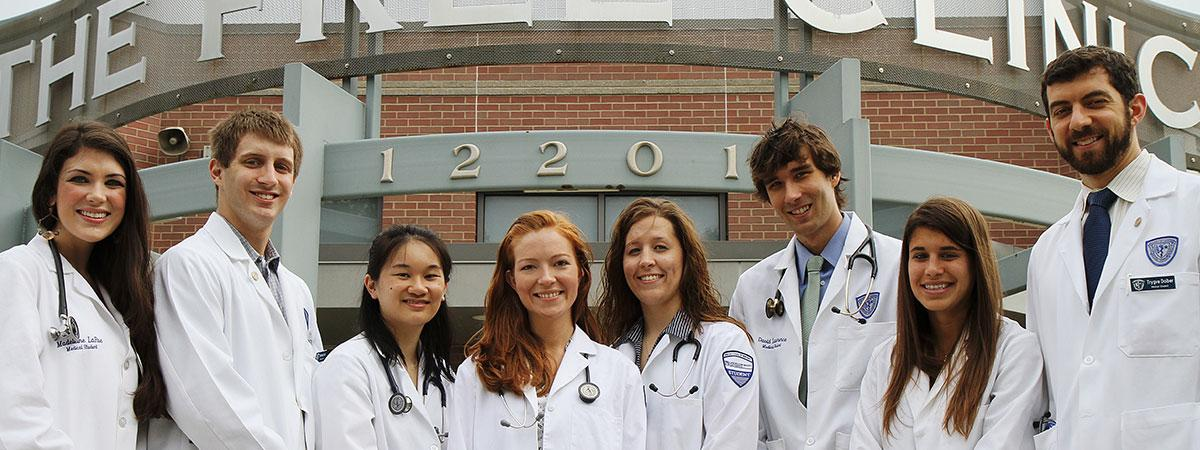 A group of student doctors standing in front of the clinic.