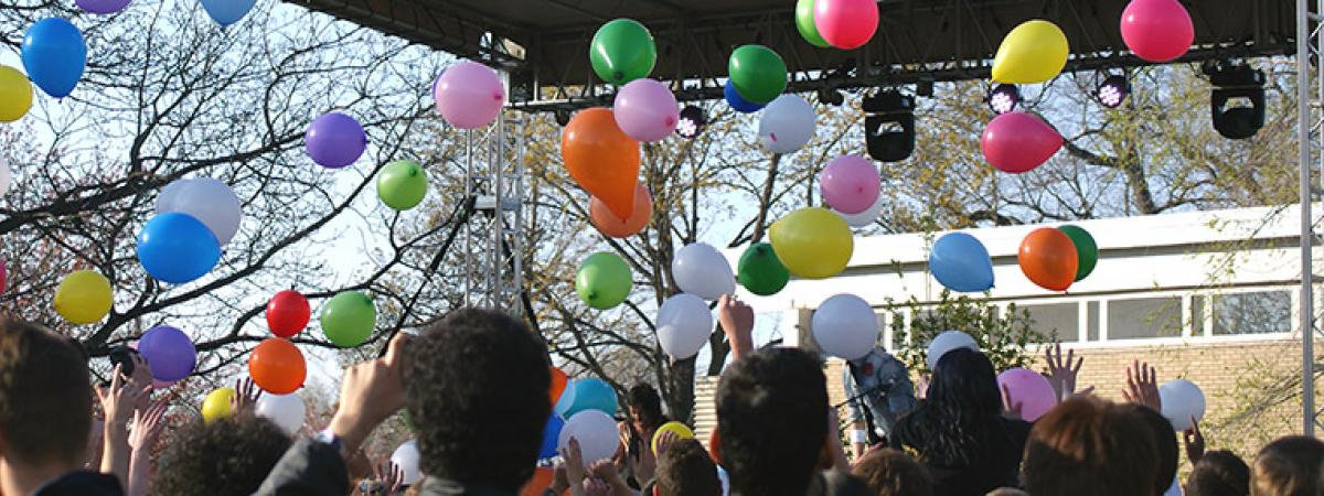 Students, balloons, and a stage during a lively event