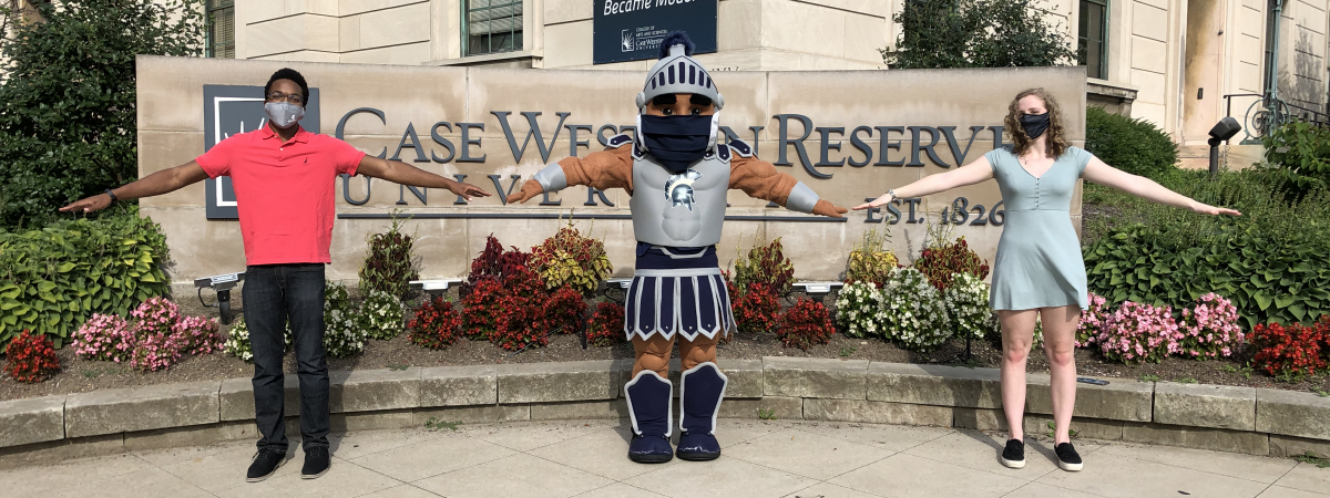 Masked Spartie with students in front of CWRU sign