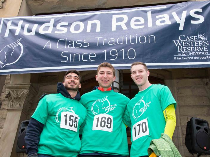 Three students in front of the Hudson Relays banner on Adelbert Hall