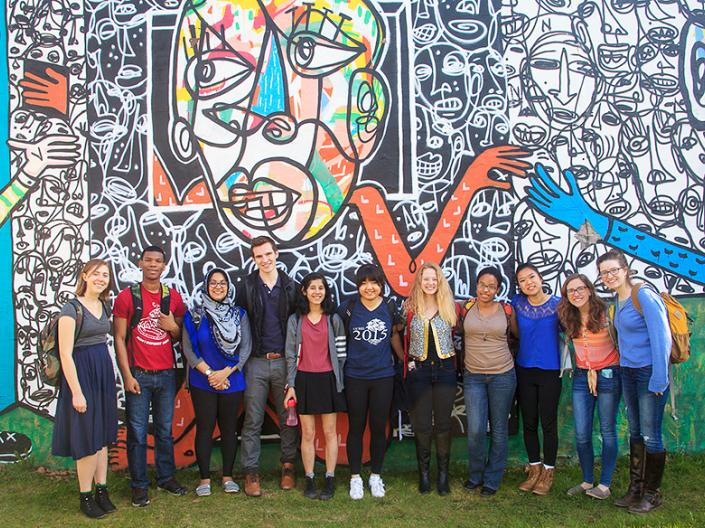 CCEL Fellow students standing in front of a mural