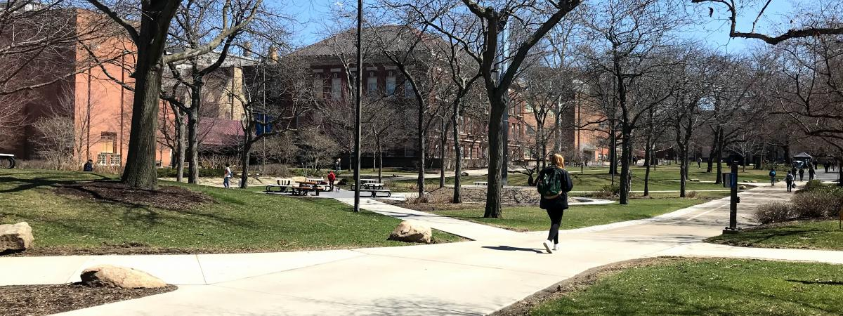 A college student walks across the Case Western Reserve University main quad in early spring