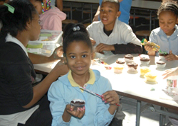 Young girl decorating a cupcake