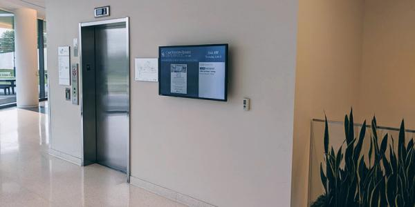 An infoboard display beside an elevator door in Tinkham Veale University Center at Case Western Reserve University