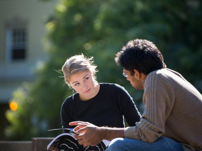 Two students talking and studying outside