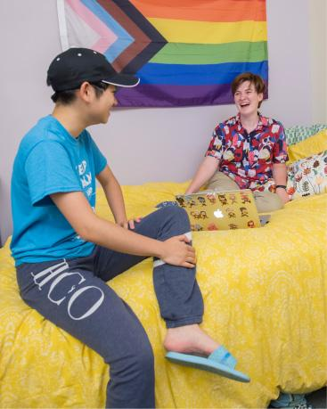 Two students sitting on a dorm bed in front of a flag with a rainbow of colors