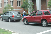 Two cars parallel parked outside a red brick building