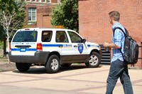 Student walking past a security vehicle parked near a red brick building