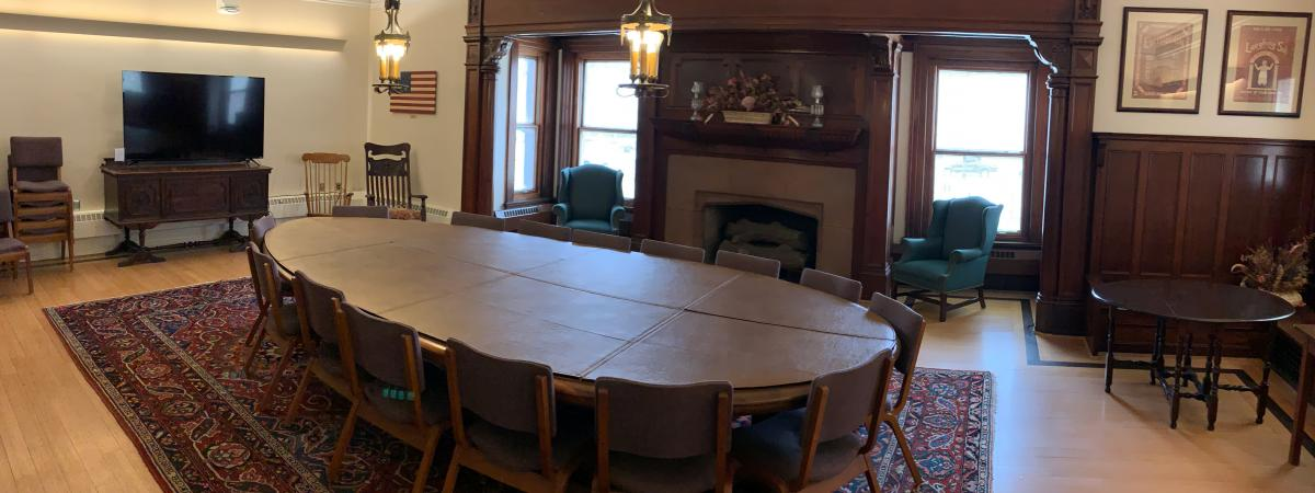An empty view of the Cleveland Room with its large round conference table and a television.
