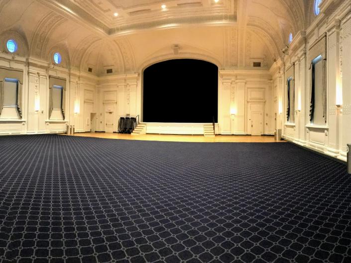 An empty view of Excelsior Ballroom with its large open floor and stage.