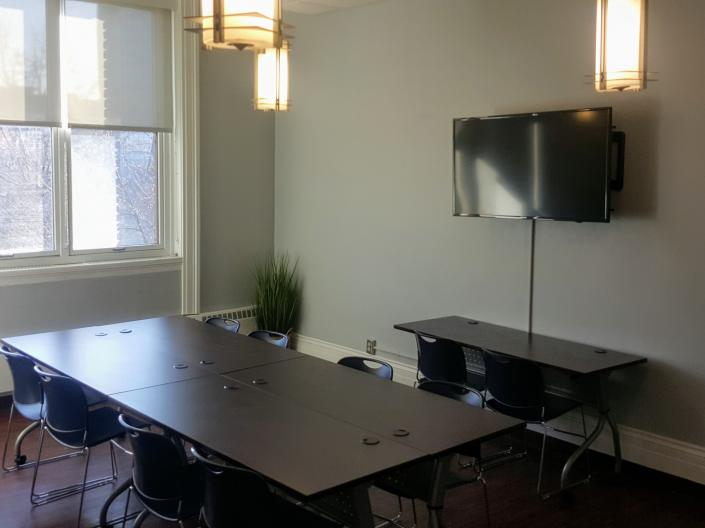 An empty view of Meeting Room 206 with its table and chairs and a television.