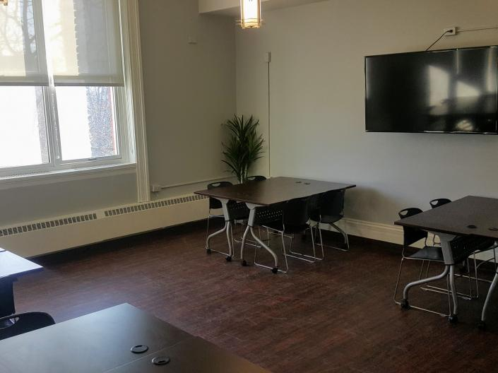 An empty view of Meeting Room 218, with four pods of tables with chairs and a television.