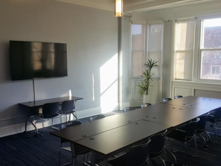 An empty view of Meeting Room 224 with its large table and chairs, large window, and television.