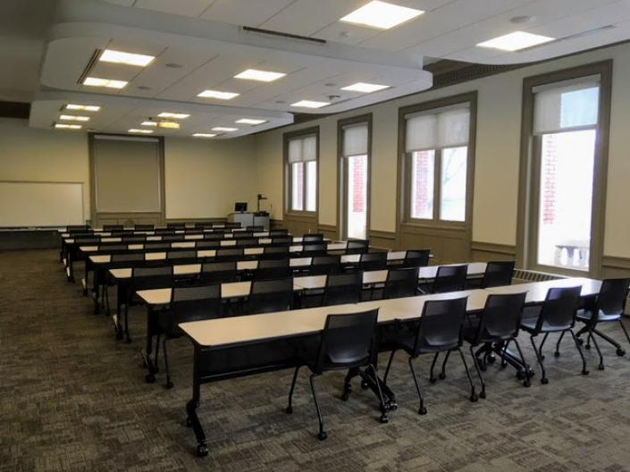 An empty view of Room 201, with several rows of tables and chairs facing the front of the room.
