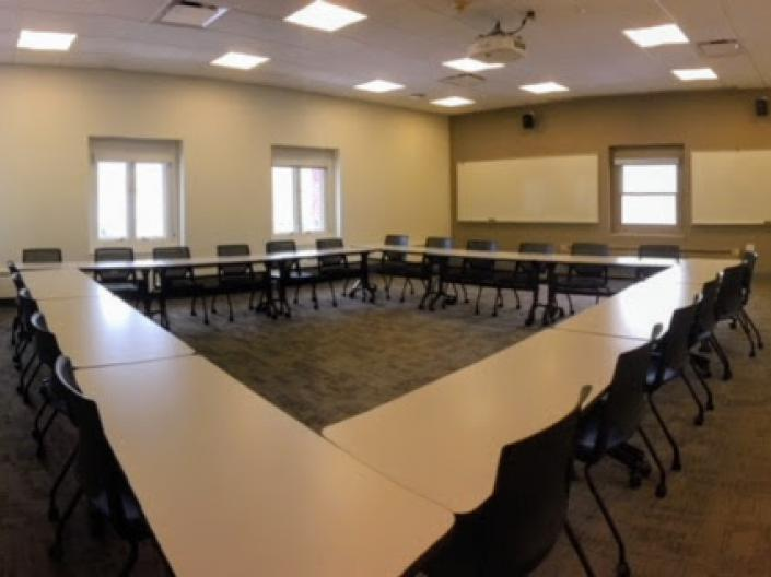 Empty photo of Room 302, with tables set up in a rectangle and chairs around them.