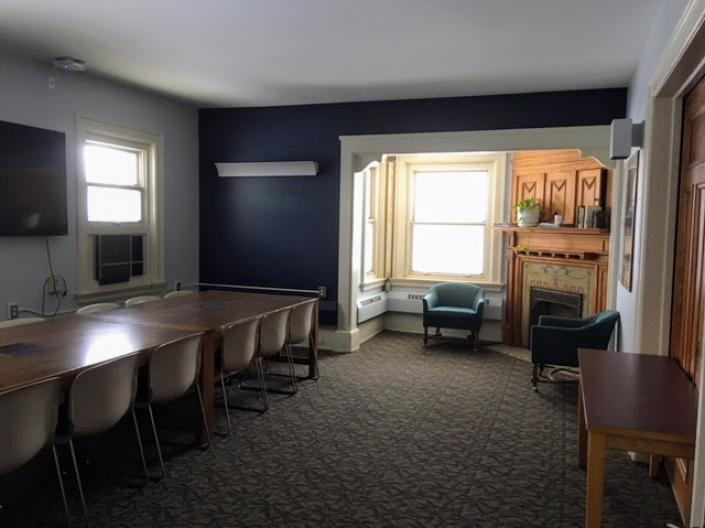 Empty view of the Spartan Room, including a large table with chairs, two cushioned chairs, a fireplace, and a television.