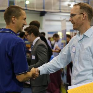 A student and employer shake hands at a Career Fair
