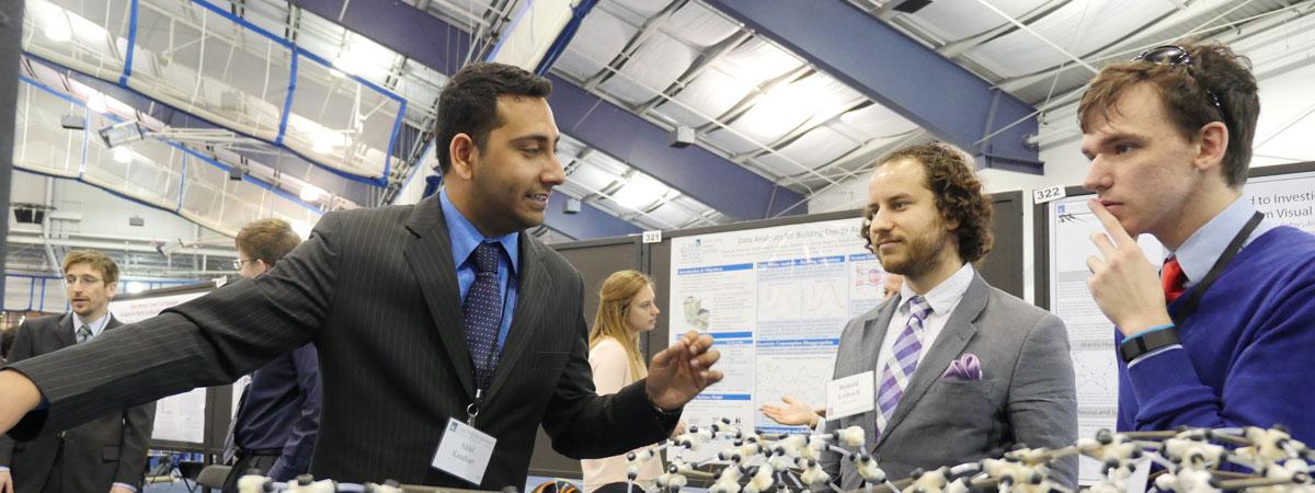 Case Western Reserve University students discussing a research model at research ShowCase