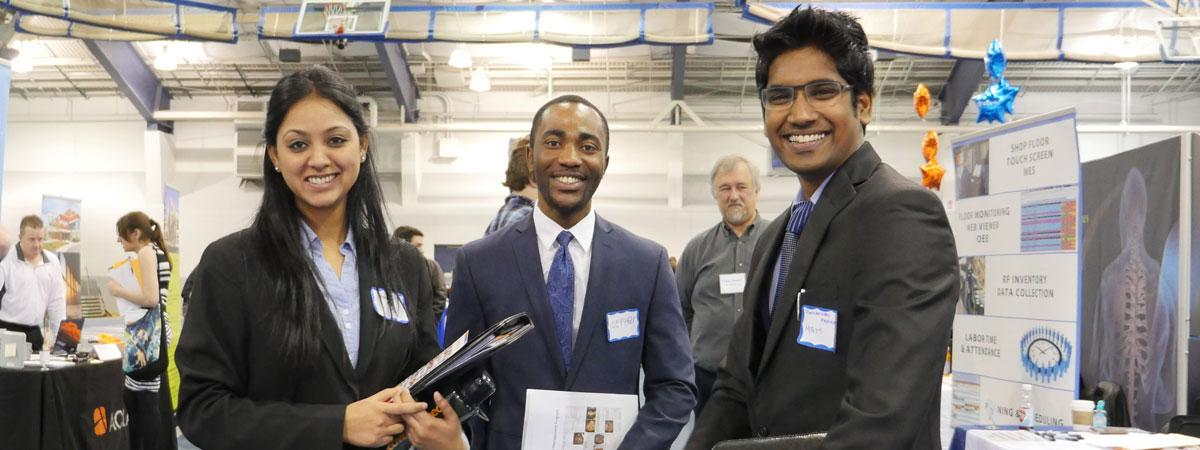 Case Western Reserve University students smiling and standing near booths at a career fair