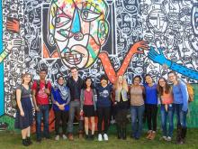 group of ccel fellows students standing in front of a mural at a volunteer site