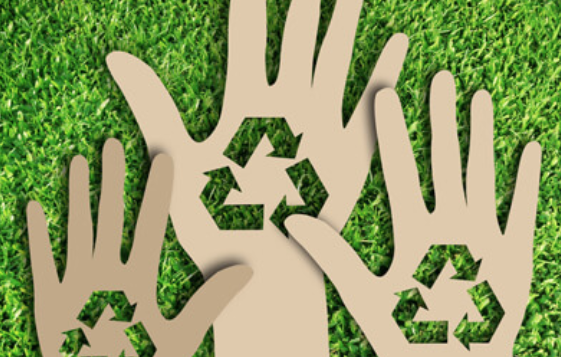cardboard hands with recycling symbols cut out of them on green grass