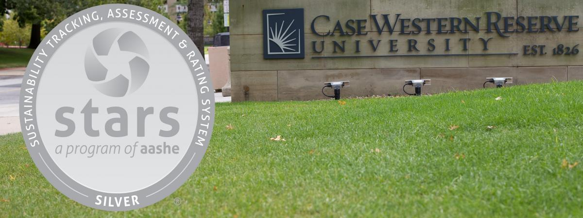 CWRU outdoor sign with grass with AASHE STARS silver logo on the left