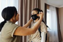 mom is placing face mask on child
