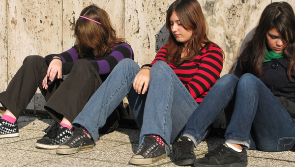 teenage girls sitting against a wall