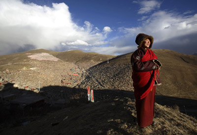 A Buddhist nun enjoys the fresh air outside the Serthar Wuming Buddhist Study Institute (elevation: 12,100 feet) in Tibet.