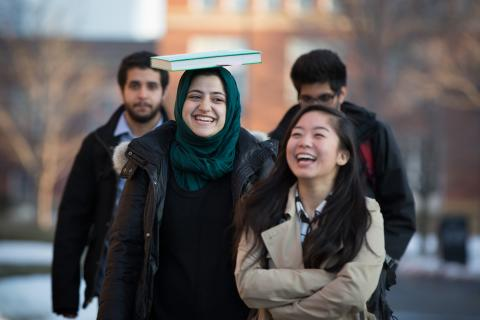 Students walking and laughing, one balancing a book on her head.