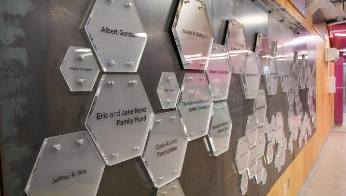 A wall in the think[box] that shows donor plaques.
