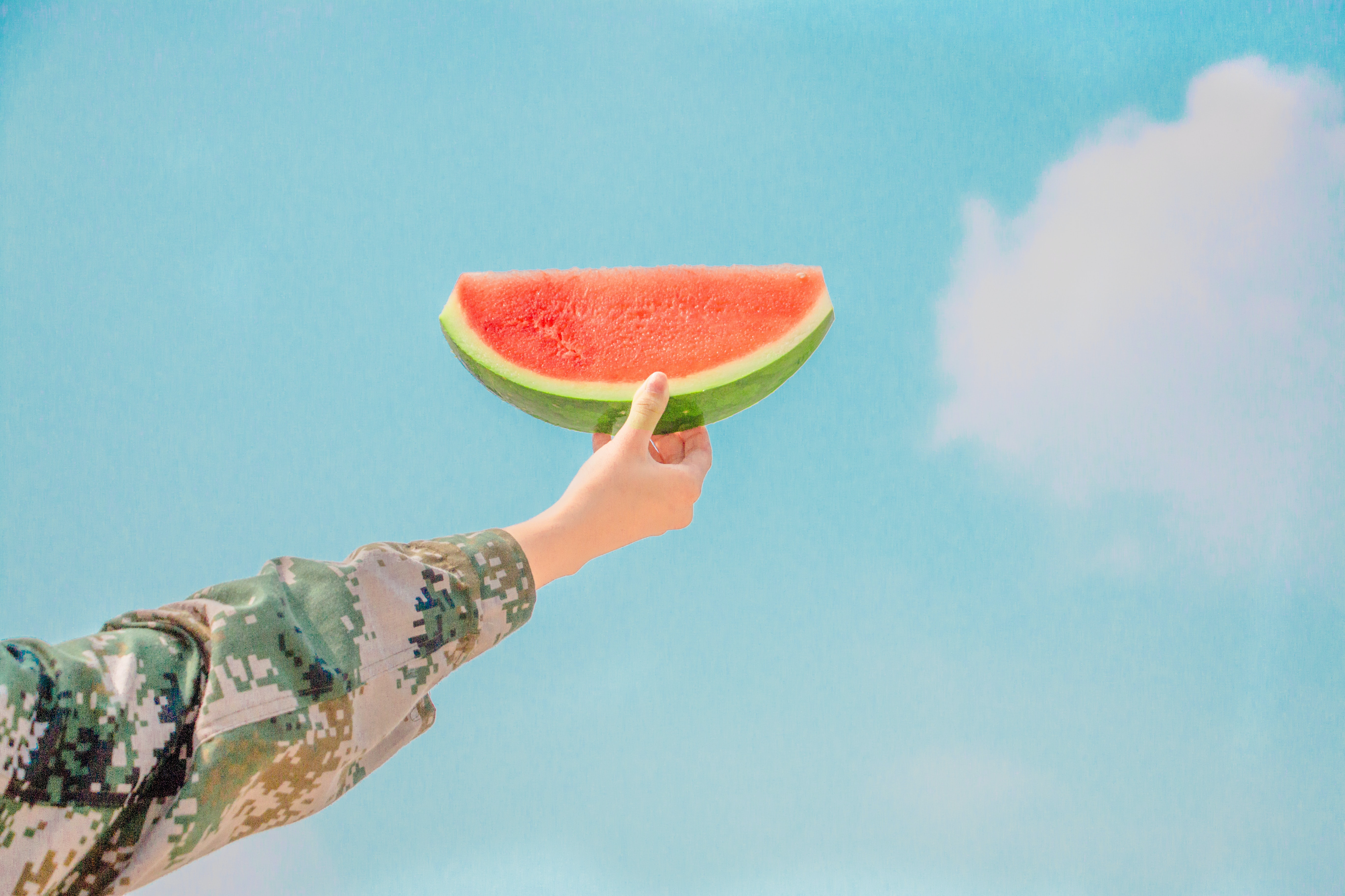 Person holding watermelon slice to the summer sky