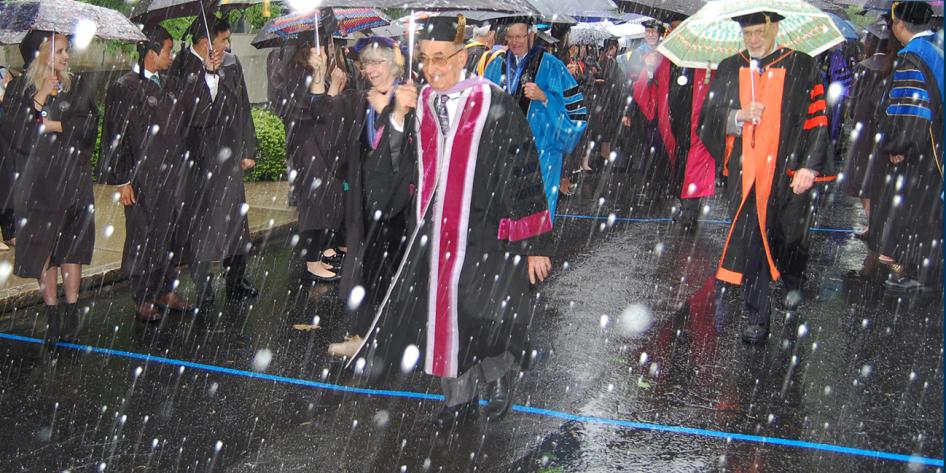 Case Western Reserve University Commencement 2016 staff and graduating students walking with umbrellas in snow