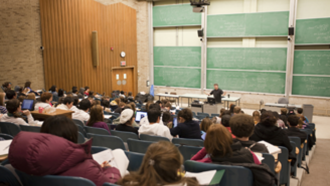 Full lecture hall with students listening to Professor