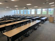 View of the classroom from the front left with row of tables with chairs