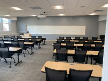 Picture of the classroom from the back right with tables and chairs, whiteboard, and lectern.
