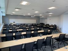 Picture of the classroom from back left showing tables and chairs, whiteboard and lectern.