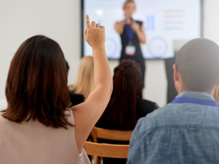 Woman raising her hand at a presentation.
