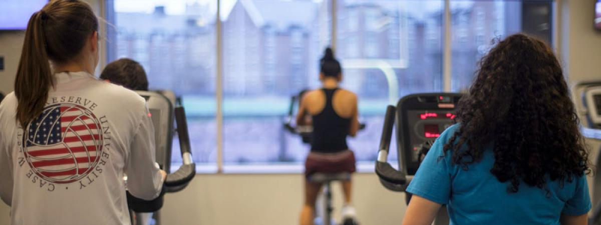 Three women with backs to camera using exercise bikes in CWRU's Wyant Center