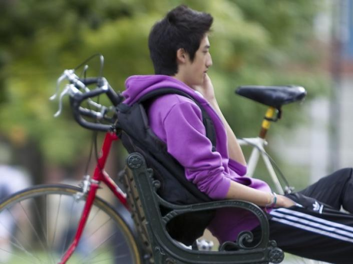A male Case Western Reserve University student sitting next to a bike